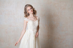 摆在婚礼发型和礼服葡萄酒的美丽的新娘 免版税库存图片