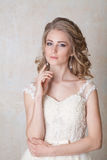 摆在婚礼发型和礼服葡萄酒的美丽的新娘 免版税库存照片