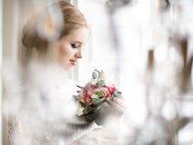 摆在婚礼礼服的年轻美丽的白肤金发的妇女 免版税库存图片