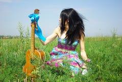 摆在嬉皮的画象室外与吉他 免版税图库摄影