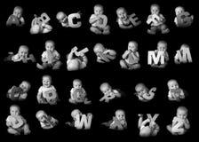 摆在字母表信件的婴孩 库存照片