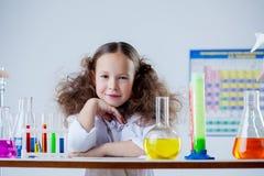 摆在实验室的微笑的可爱的女孩画象  免版税库存图片