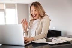 摆在家坐的美丽的白肤金发的妇女户内使用手提电脑谈的挥动 库存照片