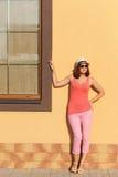 摆在对墙壁的年轻时髦的妇女 免版税库存照片