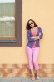 摆在对墙壁的年轻时髦的妇女 免版税图库摄影