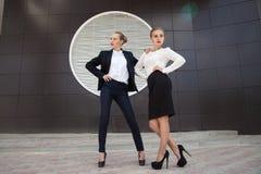 摆在对大厦墙壁的两名时髦的妇女 库存图片