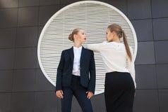 摆在对大厦墙壁的两名时髦的妇女 免版税库存图片