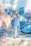 摆在对有街道画的墙壁,太阳,牛仔裤的女孩站立在被绘的墙壁 库存图片