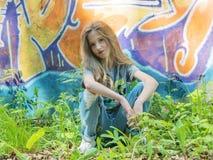 摆在对有街道画的墙壁,太阳,牛仔裤的女孩站立在被绘的墙壁 图库摄影