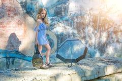 摆在对有街道画的墙壁,太阳,牛仔裤的女孩站立在被绘的墙壁 免版税图库摄影