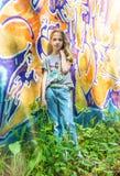 摆在对有街道画的墙壁,太阳,牛仔裤的女孩站立在被绘的墙壁 免版税库存照片
