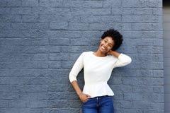 摆在对灰色墙壁的微笑的年轻非洲妇女 库存图片