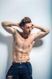 摆在对白色墙壁的性感的肌肉赤裸上身的人 库存照片