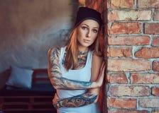 摆在对砖墙的T恤杉和帽子的一个tattoed性感的金发碧眼的女人 免版税库存图片