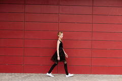 摆在对红色墙壁的一件黑礼服的美丽的白肤金发的女孩 库存照片