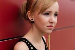 摆在对红色墙壁的一件黑礼服的美丽的白肤金发的女孩 免版税图库摄影