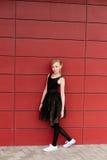 摆在对红色墙壁的一件黑礼服的美丽的白肤金发的女孩 免版税库存图片