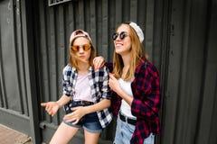 摆在对街道墙壁的两件快乐的滑稽的女孩佩带的方格的衬衣在街道 图库摄影