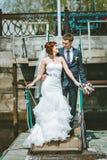 摆在小小海湾的已婚夫妇 新娘愉快日的新郎他们的婚礼 免版税库存图片