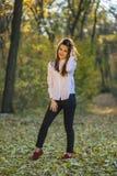 摆在小径的微笑的女孩在森林里 免版税图库摄影