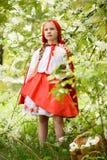 摆在小红骑兜帽礼服的微笑的白肤金发的女孩在绿色树附近 免版税库存照片