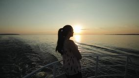 摆在小船的一个美丽的女孩的侧视图在日落时间鞠躬 股票录像