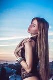 摆在屋顶的美丽的性感的白肤金发的时尚妇女 免版税图库摄影
