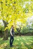 摆在山毛榉树下的年轻深色的妇女在秋天 库存照片