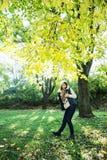 摆在山毛榉树下的正面深色的妇女在秋天 图库摄影