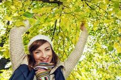 摆在山毛榉树下的美丽的微笑的浅黑肤色的男人在秋天 库存图片