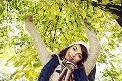 摆在山毛榉树下的美丽的白种人妇女在秋天 免版税图库摄影