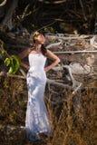 摆在山的热带树中间的新娘 免版税库存照片