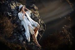 摆在山的美丽的时装模特儿妇女在日落 免版税图库摄影