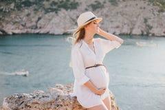 摆在山的年轻美丽的孕妇在海附近 免版税库存照片