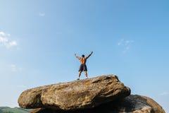 摆在岩石的后面观点的坚强的黑人爱好健美者反对蓝色多云天空 图库摄影