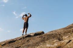 摆在岩石的后面观点的英俊的非裔美国人的爱好健美者反对蓝色多云天空 库存图片
