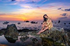 摆在岩石的性感的亚裔女孩在日落 免版税库存照片