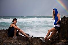摆在岩石风雨如磐的年轻人的夫妇海&# 免版税库存图片