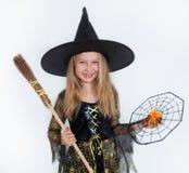 摆在巫婆礼服,万圣夜的女孩 库存图片