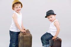 摆在带着巨大的手提箱的两个兄弟 图库摄影