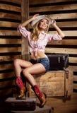 摆在帽子的一个性感的女牛仔 免版税库存照片