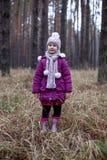 摆在干草的秋天森林里的逗人喜爱的小女孩 免版税图库摄影