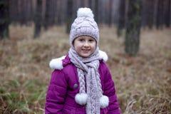 摆在干草的秋天森林里的逗人喜爱的小女孩 免版税库存图片