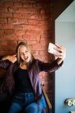 摆在年轻快乐的妇女,当拍摄在闲谈的聪明的电话照相机与她的朋友,有吸引力的微笑的臀部时 免版税图库摄影