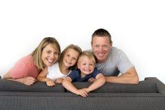 摆在年轻有吸引力和愉快的夫妇在家坐沙发co 库存照片