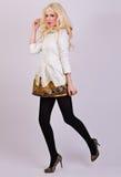 摆在庄重装束的美丽的白肤金发的女孩在演播室 免版税库存图片