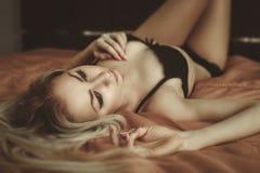 摆在床上的性感的女用贴身内衣裤的年轻可爱的白肤金发的妇女。Vo 免版税库存图片