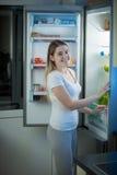 摆在开放冰箱的微笑的妇女画象晚上 图库摄影