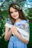 摆在开花的夏天庭院里的愉快的少妇 免版税库存图片