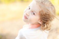 摆在微笑的孩子的女孩户外 库存照片